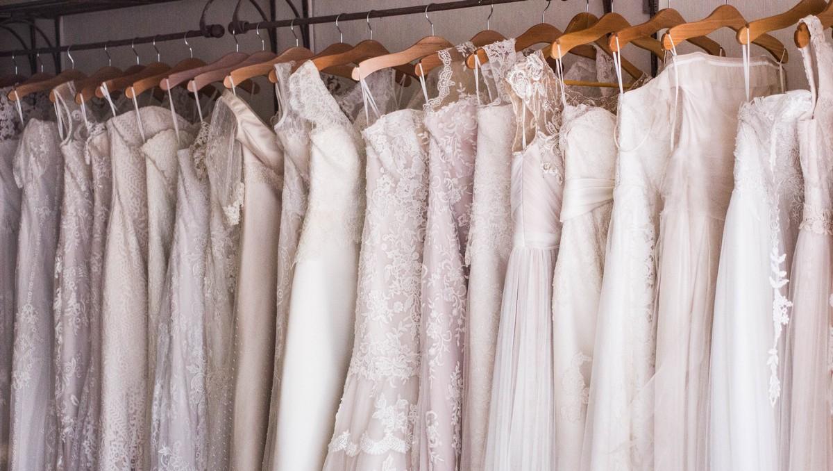 Svatební šaty ve svatebním salonu vystavené na ramínkách.